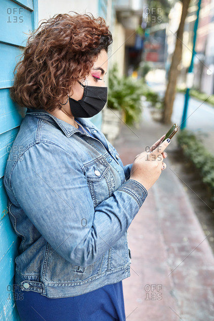 Side view of plus size female wearing protective mask standing in narrow street near residential building and browsing smartphone during COVID 19 epidemic in city
