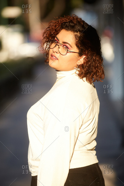 Side view of plump female wearing trendy clothes and glasses standing in city on sunny day and confidently looking at camera