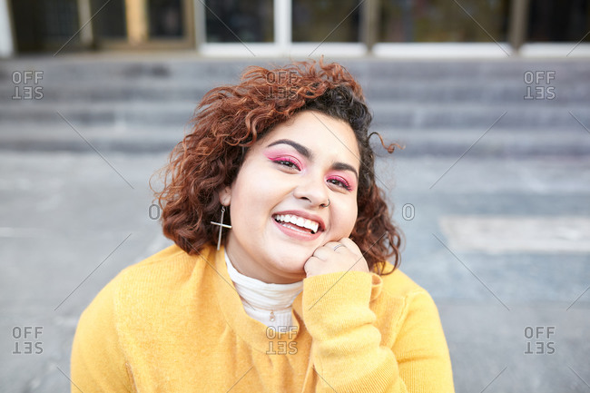 Content plus size female in casual wear sitting on stairs in city and looking at camera while enjoying sunny weather at weekend and touching curly hair