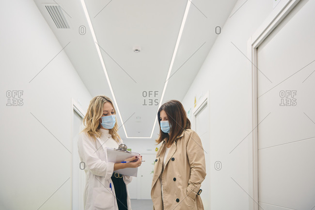 Female client in mask talking to beautician standing with clipboard in white corridor of modern beauty center