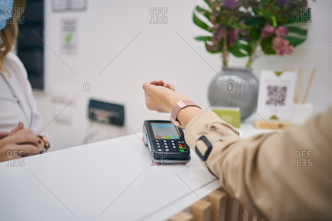 Unrecognizable female client making payment on POS terminal with smart watch in beauty center