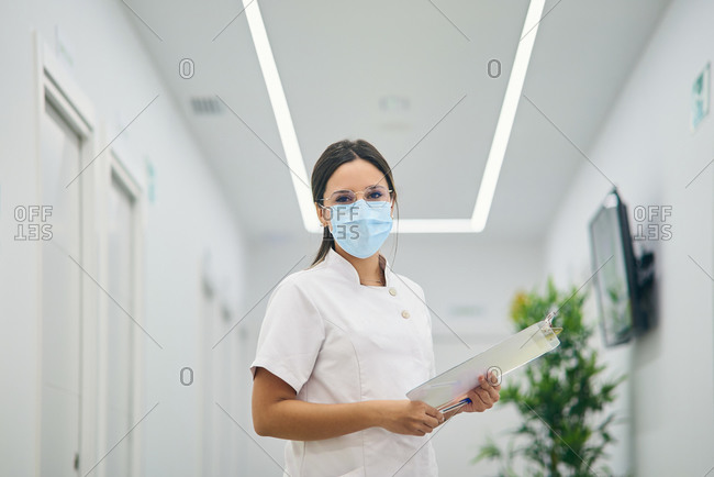 Female dermatologist in uniform and medical mask standing with clipboard in hallway of modern beauty center and looking at camera
