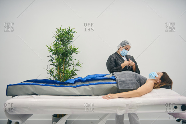 Woman in costume for pressure therapy lying on medical table and talking to beautician in mask in contemporary beauty clinic
