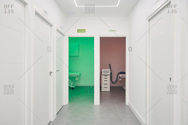 Interior of white hallway of beauty salon with rooms with various appliances for skin care treatment illuminated by red and green neon lights