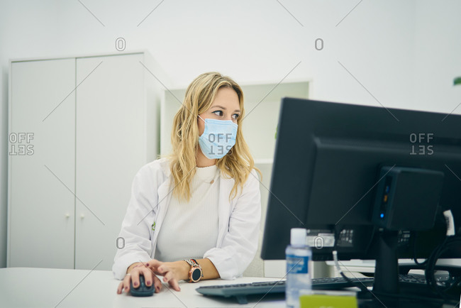 Female dermatologist in mask using computer in bright room while working in modern beauty clinic