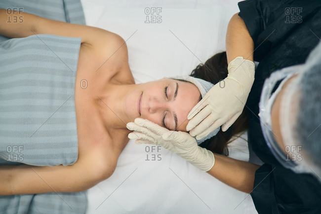 From above of beautician in gloves doing face massage for relaxed female client lying on table in beauty clinic
