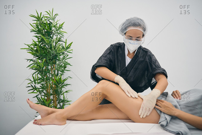Professional masseuse doing anti cellulite massage on legs of female client while using special machine in modern beauty clinic