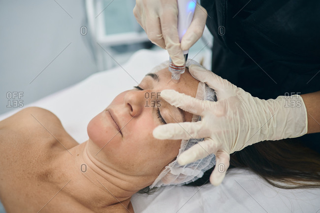 Crop dermatologist using machine for cleansing pores on face of mature female lying on table in beauty center