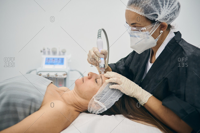 Dermatologist wearing protective face mask using machine for cleansing pores on face of mature female lying on table in beauty center during covid 19 pandemic