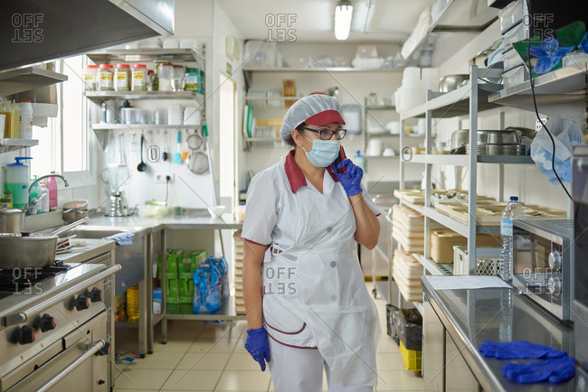 Female cook in white uniform and protective mask and gloves speaking on smartphone while working in hospital kitchen during coronavirus pandemic