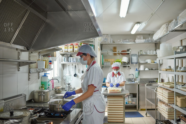 Professional female cook in white uniform and protective mask and gloves preparing food on stove while working with colleague in hospital kitchen during coronavirus pandemic