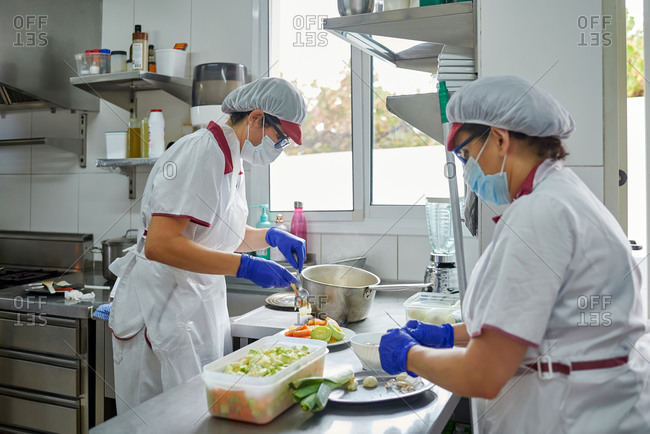 Side view of unrecognizable female cooks in protective masks and gloves preparing meal for patients while working in hospital kitchen during coronavirus pandemic