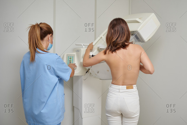Female medic in masks and uniform preparing woman with naked torso for chest radiology while standing in medical room in clinic