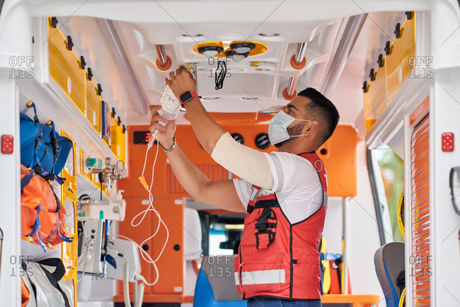 Side view of serious male paramedic in medical mask standing with dropper in modern ambulance van