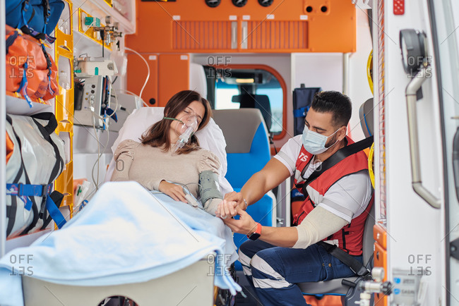 Paramedic putting finger pulse oximeter on patient in ventilator mask lying on medical stretcher in ambulance car
