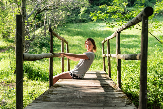 Calm female sitting on old bridge over river in woods and enjoying nature in summer