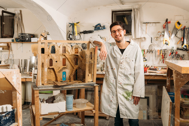 Young delighted male artisan standing near handmade exterior of clay building in workshop and looking at camera