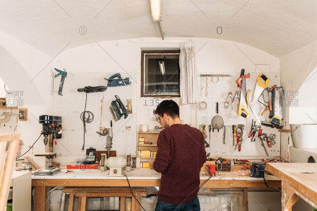 Back view of male woodworker standing at workbench and creating wooden details in bright garage