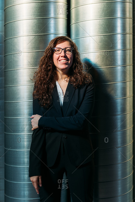 Delighted female entrepreneur in formal clothes standing in modern storehouse and leaning on metal barrel while looking at camera