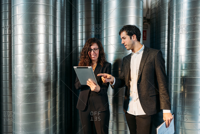 Busy male and female colleagues in formal clothes using tablet together while working in storehouse with metal barrels