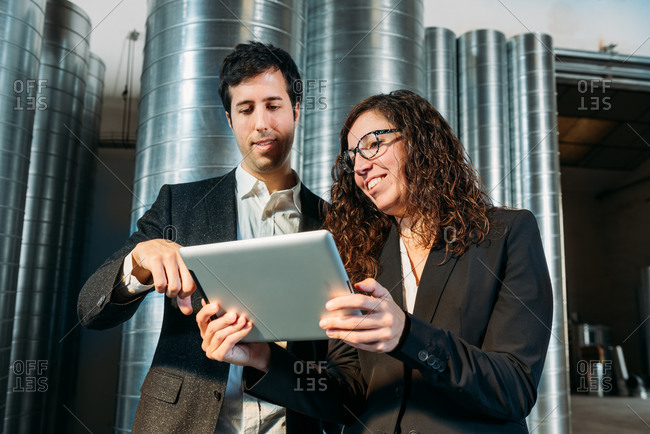 Low angle of smart coworkers in formal suits standing in modern warehouse and discussing business issues while using tablet together