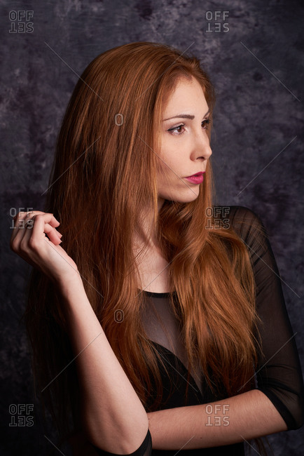 Calm female model in stylish clothes standing in studio with red hair and looking away