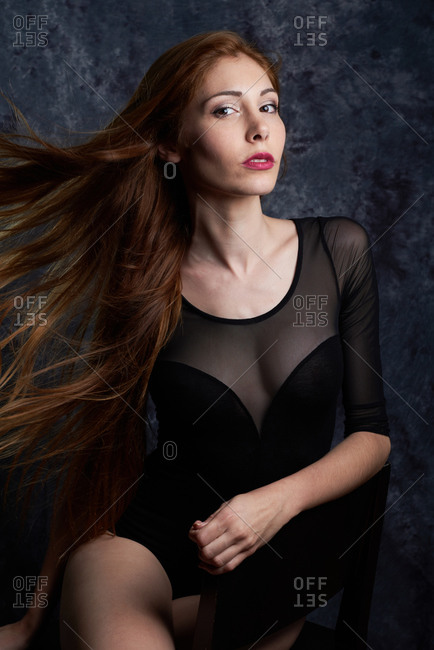 Calm female model in stylish clothes sitting in chair in studio with red flying hair and looking at camera
