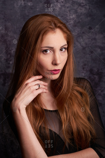 Calm female model in stylish clothes standing in studio with red hair and looking at camera