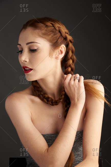 Stylish female model with red hair and braids sitting in studio on dark background and looking away
