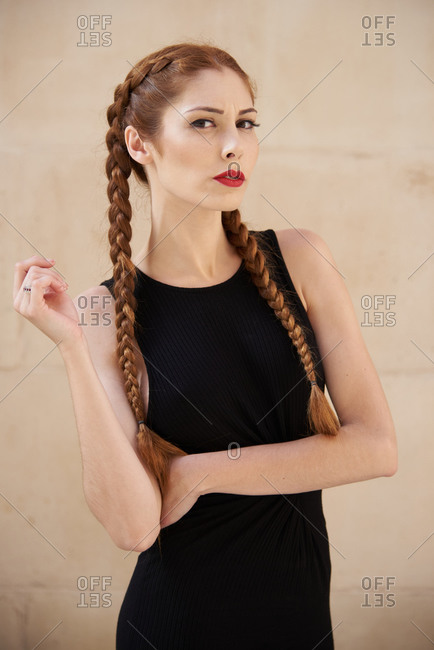Stylish female model with red hair and braids sitting in studio on dark background and looking at camera
