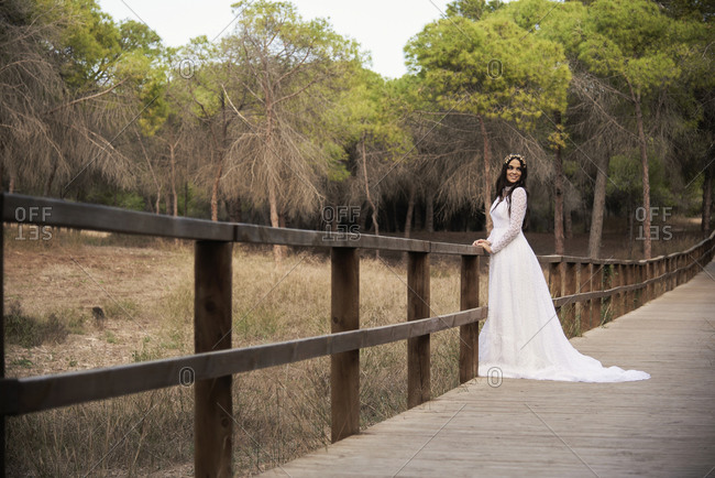 Full body side view of happy elegant young female in boho bridal maxi dress and wreath standing on wooden walkway in green woods and looking at camera
