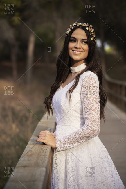 Side view of happy elegant young female in boho bridal maxi dress and wreath standing on wooden walkway in green woods and looking away