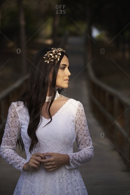 Portrait of charming tender young brunette in stylish white lace wedding dress and bridal wreath touching cheek
