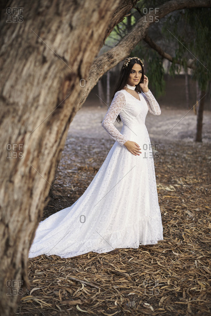 Full body side view of happy elegant young female in boho bridal maxi dress and wreath standing on wooden walkway in green woods and looking away