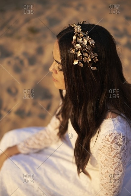 From above side view of young romantic bohemian brunette in white wedding dress and golden floral wreath sitting on sand
