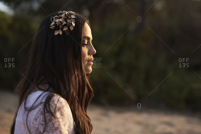 Side view of elegant young female in boho bridal maxi dress and wreath in green woods and looking away