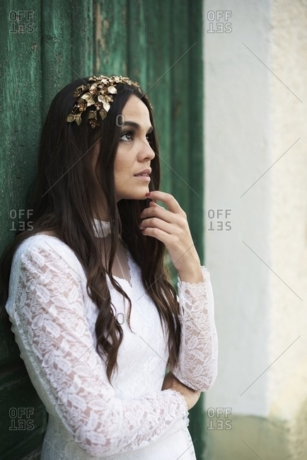 Young long haired brunette in elegant white lace bridal gown and golden wreath touching chin and looking away thoughtfully while thinking about future