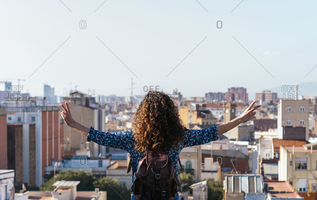 Back view of female with curly hair standing with outstretched arms on roof and showing two fingers while admiring amazing cityscape