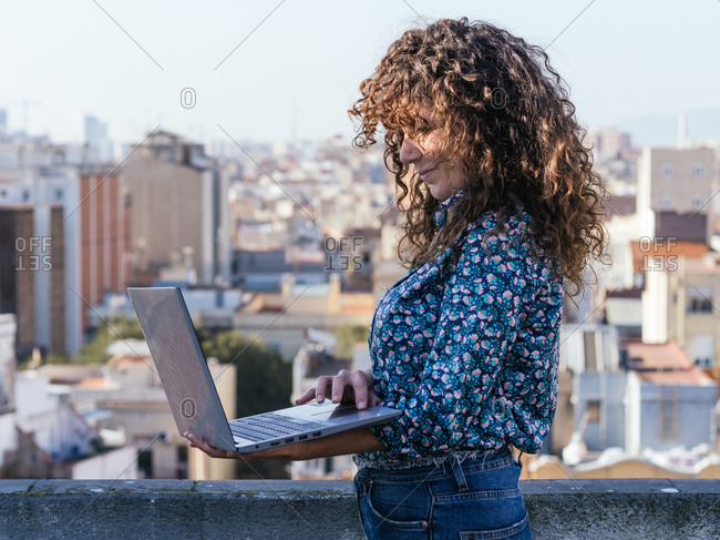 Side view of female freelancer standing on rooftop and browsing laptop while working on remote project
