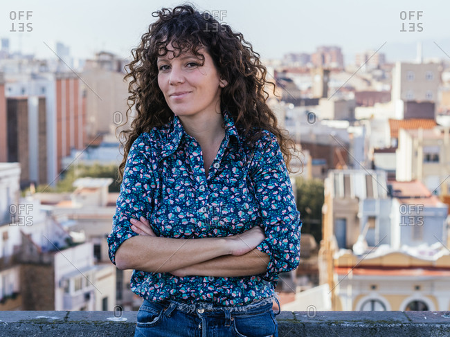 Tranquil female with long curly hair standing on roof of building against cityscape with arms crossed looking at camera while enjoying summer weekend