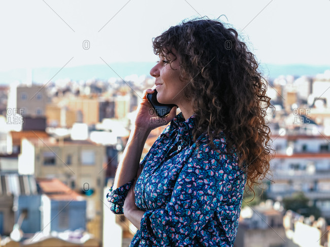 Side view of cheerful female with curly hair standing on background of cityscape and speaking on mobile phone