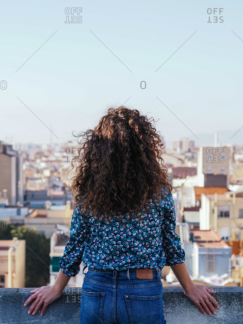 Back view of tranquil female with long curly hair standing on roof of building against cityscape while enjoying summer weekend