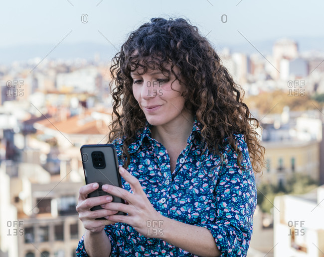 Female with curly hair standing on background of cityscape and texting on mobile phone