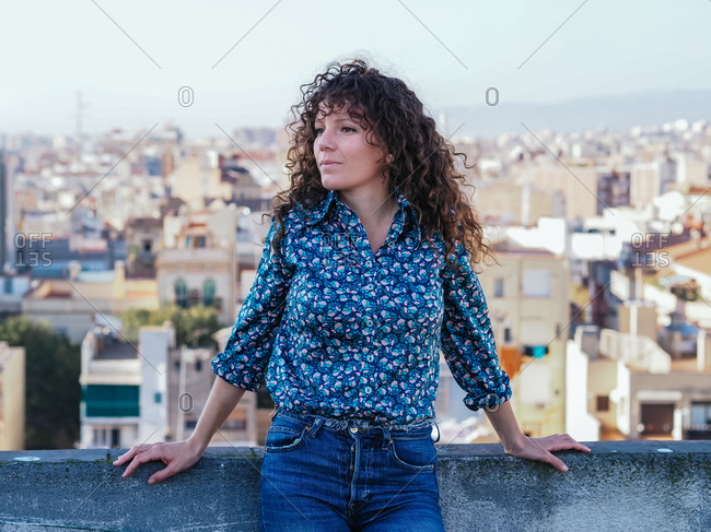 Tranquil female with long curly hair standing on roof of building against cityscape and looking away while enjoying summer weekend