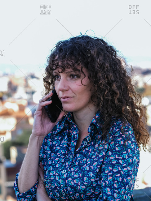 Female with curly hair standing on background of cityscape and speaking on mobile phone