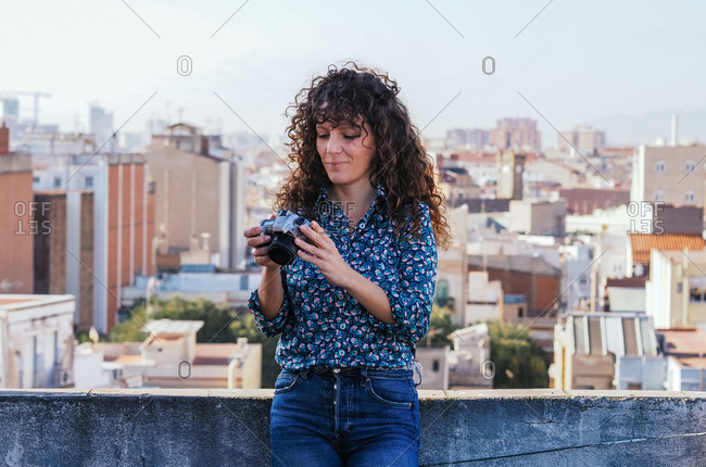 Content female photographer with modern photo camera standing on roof of building and looking through pictures on background of cityscape