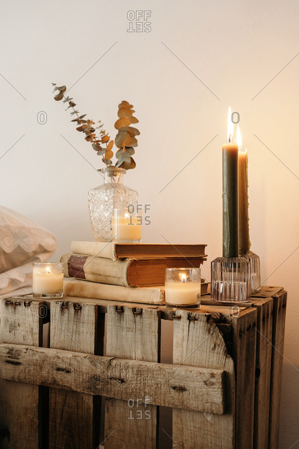 Fragment of interior of bedroom with rustic wooden handmade bedside table with dry plants in glass vase placed on stack of old books near burning candles