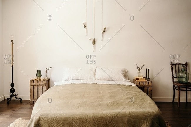 Light bedroom with minimalist interior including comfortable bed and wooden furniture with boho decoration on white wall