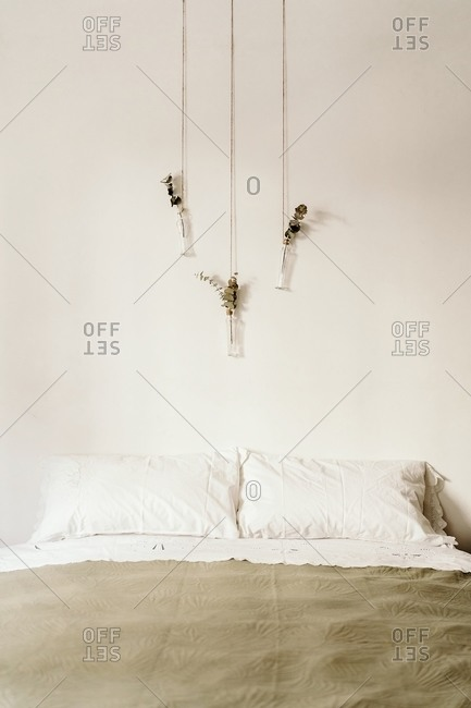 Minimalist interior of bedroom with soft bed and bohemian handmade decorations hanging on white wall