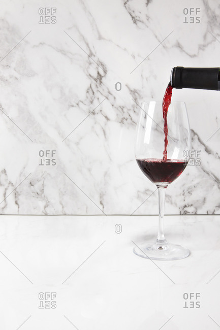 Wine being poured into a glass on a white marble countertop